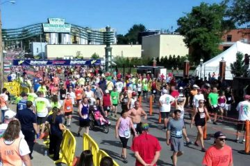 a photo of a large group of people all crossing a finish line after running a 9 mile race